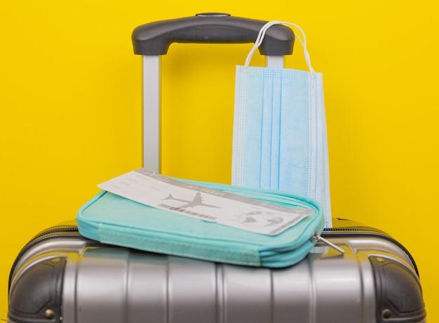 Vliegtuigkaartje medische maskers op de bagagetas