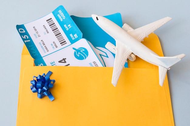 Vliegtuigkaartjes in documentgeval dichtbij speelgoedvliegtuigen