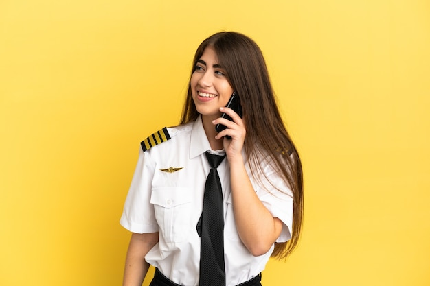 Vliegtuigpiloot geïsoleerd op gele achtergrond die een gesprek voert met de mobiele telefoon met iemand