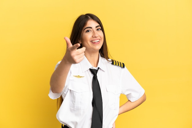Vliegtuigpiloot geïsoleerd op gele achtergrond met duimen omhoog omdat er iets goeds is gebeurd