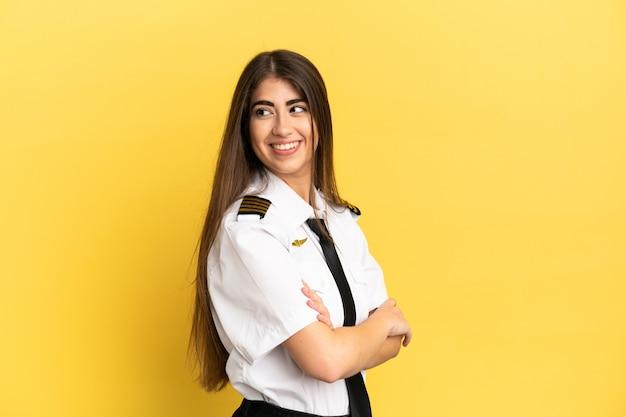 Vliegtuigpiloot geïsoleerd op gele achtergrond met gekruiste armen en happy