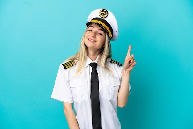 Vliegtuigpiloot over geïsoleerde blauwe achtergrond die een vinger toont en opheft in teken van het beste