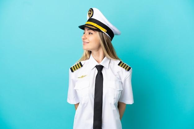 Vliegtuigpiloot over geïsoleerde blauwe achtergrond die kant kijkt