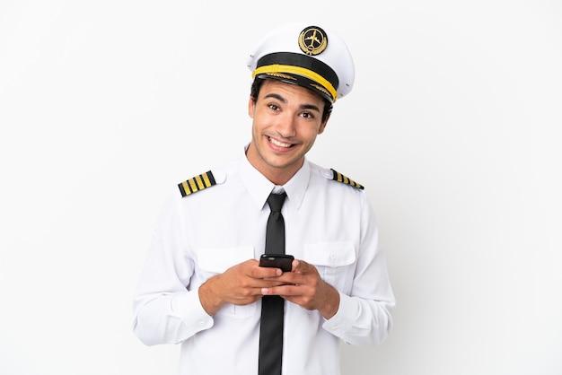 Vliegtuigpiloot over geïsoleerde witte achtergrond die een bericht met mobiel verzendt