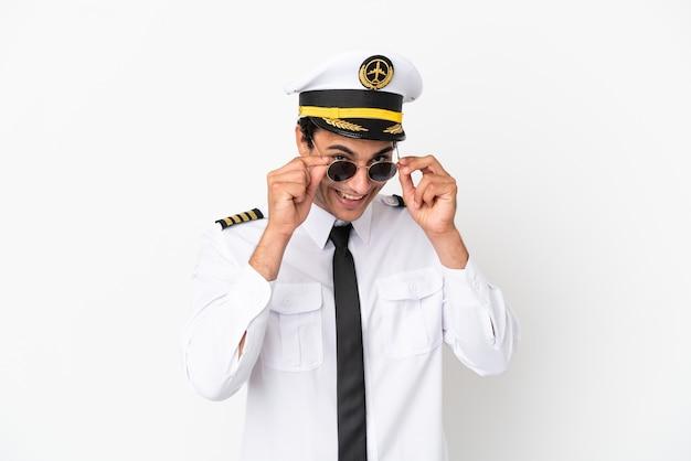 Vliegtuigpiloot over geïsoleerde witte achtergrond met glazen en verrast