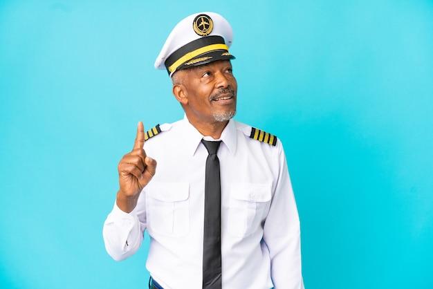Vliegtuigpiloot senior man geïsoleerd op blauwe achtergrond denken een idee met de vinger omhoog finger