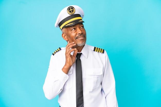 Vliegtuigpiloot senior man geïsoleerd op blauwe achtergrond die een idee denkt terwijl hij omhoog kijkt