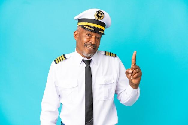 Vliegtuigpiloot senior man geïsoleerd op blauwe achtergrond met de bedoeling de oplossing te realiseren terwijl hij een vinger optilt