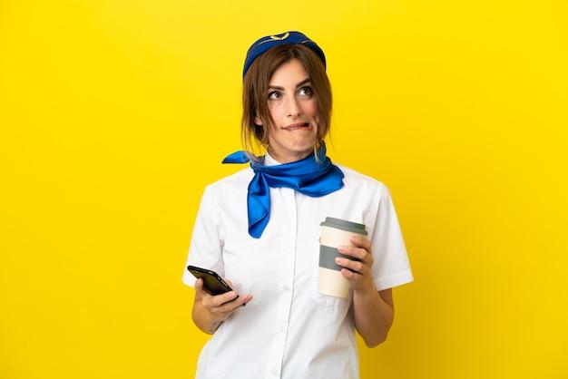 Vliegtuigstewardessvrouw geïsoleerd op gele achtergrond met koffie om mee te nemen en een mobiel terwijl ze iets denkt