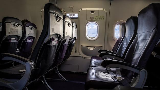 Vliegtuigstoel en ramen in een vliegtuig. uitzicht op wolken vanuit het raam van de vliegtuigpassagier. mooie witte wolk gezien door het raam van een vliegtuig.