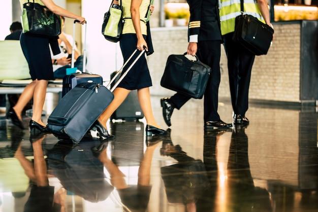Vliegtuigteam bemanning instappen scène met kapitein en gastvrouw assistent vliegen met koffers reflecterend op de vloer bij de luchthavenpoort