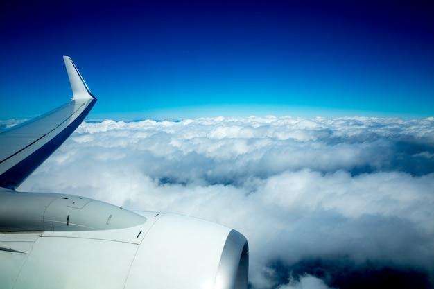 Vliegtuigvleugel die over pluizige wolken in blauwe hemel vliegen