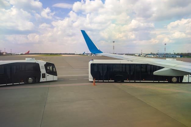 Vliegtuigvleugel en speciale bus voor het verplaatsen van passagiers van vliegtuig naar terminal.