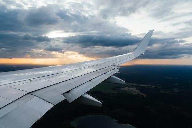 Vliegtuigvleugel en wolken vanuit het raam uitzicht