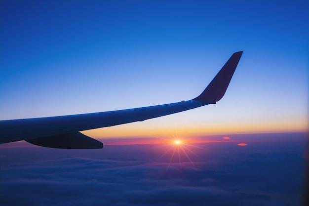 Vliegtuigvleugel met zonsopgang in lichte gloed door door het vliegtuigvenster te kijken. - afbeelding