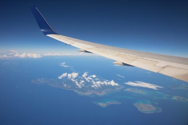 Vliegtuigvleugel over atolleneiland, oceaan, witte wolk, en blauwe hemel. reis per straalvliegtuig. luchttransport