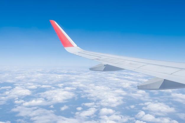 Vliegtuigvleugel, wolken en blauwe lucht hebben door het raam van een vliegtuig gezien.