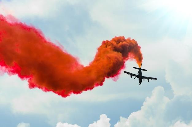 Vliegtuigvlieg in zigzaglijnen met een rode sleeprook in de hemel.