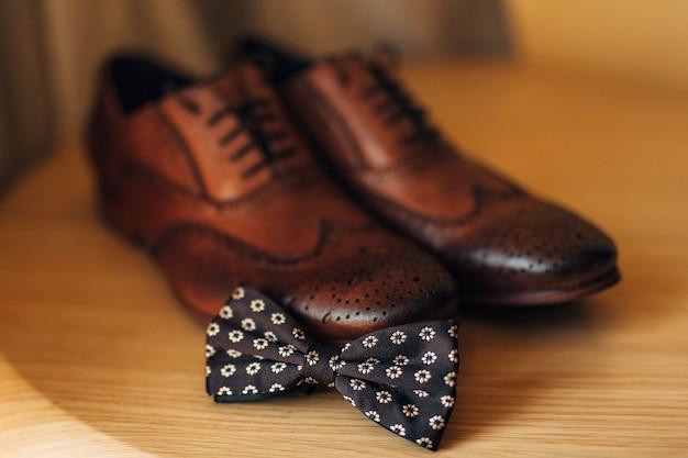 Vlinderdas en bruine schoenen