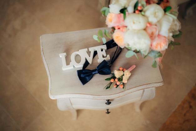Vlinderdas en corsages op een houten tafel