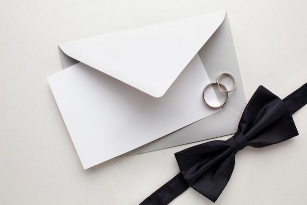 Vlinderdas en enveloppen bewaren het concept van het datumhuwelijk
