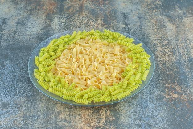 Vlinderdas en fusilli pasta in de kom, op de marmeren achtergrond.