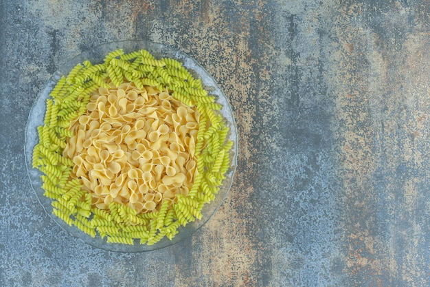 Vlinderdas en fusilli pasta in de kom, op het marmeren oppervlak.