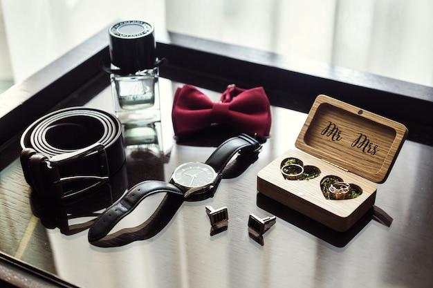 Vlinderdas, trouwringen, riem, klok, parfums, manchetknopen, de bruidegomochtend, zakenman, bruiloft, mannenmode, herenaccessoires