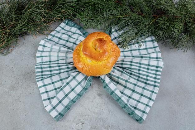 Vlindervormige handdoek onder een zoet broodje op een marmeren ondergrond