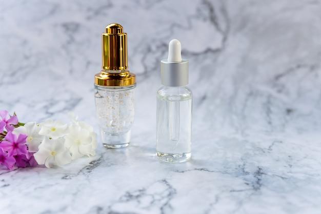 Vloeibaar collageen of hyaluronzuur met pipet in glazen fles, op marmeren achtergrond