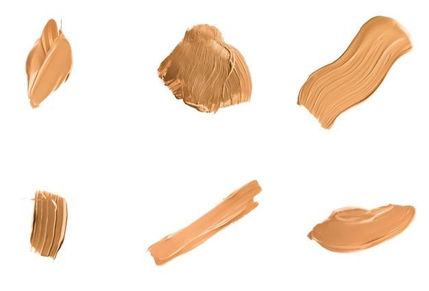 Vloeibare foundation veegt uitstrijkjes en slagen als make-up texturen geïsoleerd op een witte achtergrond schoonheid ...