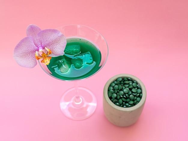 Vloeibare groene spirulina-drank met phalaenopsis in cocktailglas en spirulina-pillen