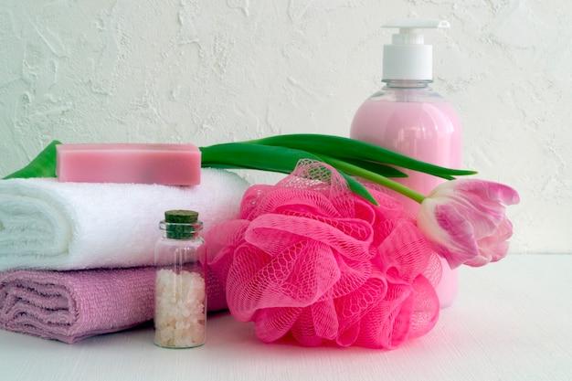 Vloeibare zeep en twee handdoeken op een witte achtergrond.