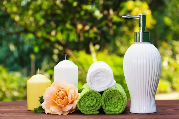 Vloeibare zeep, stapel handdoeken, kaarsen en geurige roos