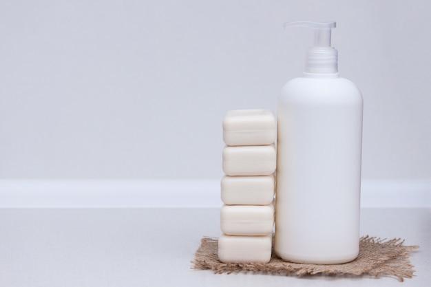 Vloeistof en zeepstaaf op de witte achtergrond. ruimte kopiëren