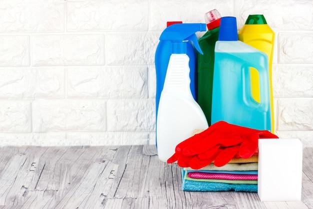 Vloeistof, pasta, gel in plastic containers. borstel, spons, microfiber servet en rode rubberen handschoenen