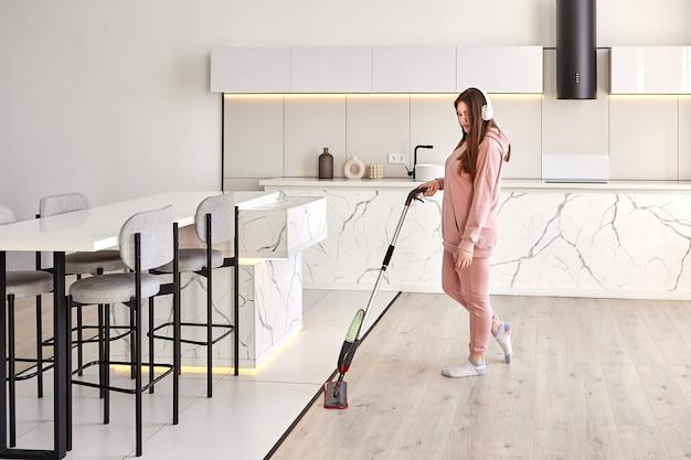 Vloer wassen met platte dweilmop meid veegt de vloer af met een vochtige doek terwijl ze naar muziek luistert via een koptelefoon