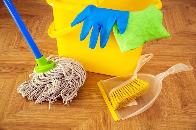 Vloerreinigingszwabber en blauwe handschoenen op een gele emmer. de stofzuiger zorgt voor hygiëne in huis