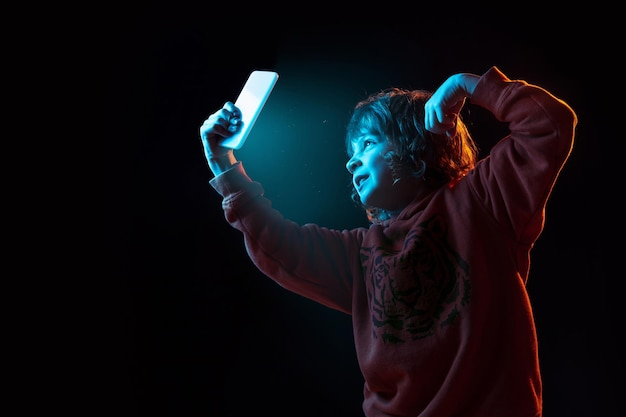 Vloggen met smartphone. het portret van de kaukasische jongen op donkere studioachtergrond in neonlicht. prachtig model met krullend haar.