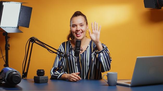 Vlogger begroet het publiek en begint een nieuwe cameralens te beoordelen in haar professionele studioset. contentmaker nieuwe media ster influencer op sociale media pratende video-fotoapparatuur voor online