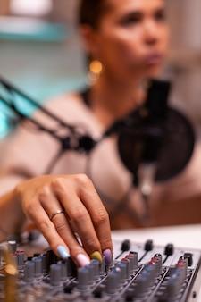 Vlogger controleert geluid op mixer terwijl hij spreekt in vlog-aflevering voor volgers