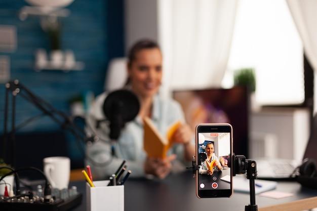 Vlogger houdt boek vast tijdens podcastreview op sociale media. beïnvloeder van creatieve inhoud die live video streamt en digitale communicatie via sociale media opneemt voor haar publiek
