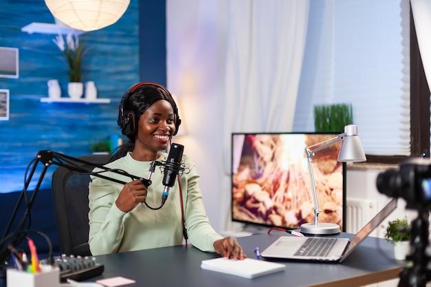 Vlogger praat met haar publiek terwijl ze een online show maakt vanuit de woonkamer. sprekend tijdens livestreaming, blogger discussiërend in podcast met koptelefoon op.