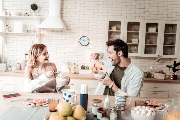 Vlokken. bebaarde knappe positieve man in een wit overhemd op zoek vrolijk tijdens het eten van vlokken voor het ontbijt