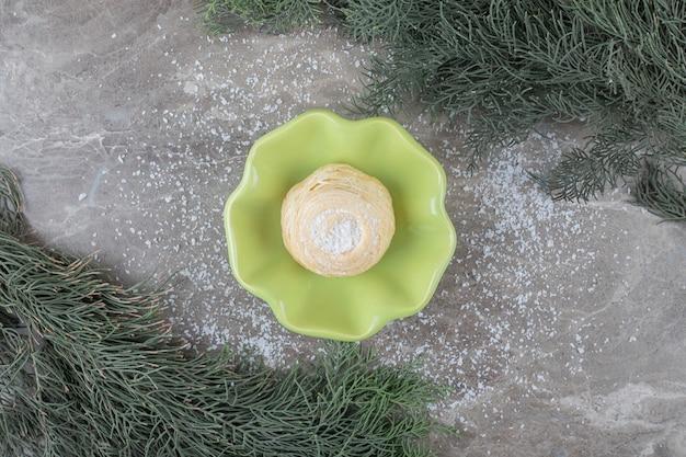 Vlokkig koekje in een kleine kom tussen pijnboomtakken op marmeren oppervlak