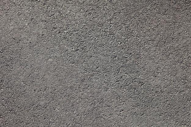Vlotte donkergrijze de textuurachtergrond van de asfaltbestrating met kleine rotsen
