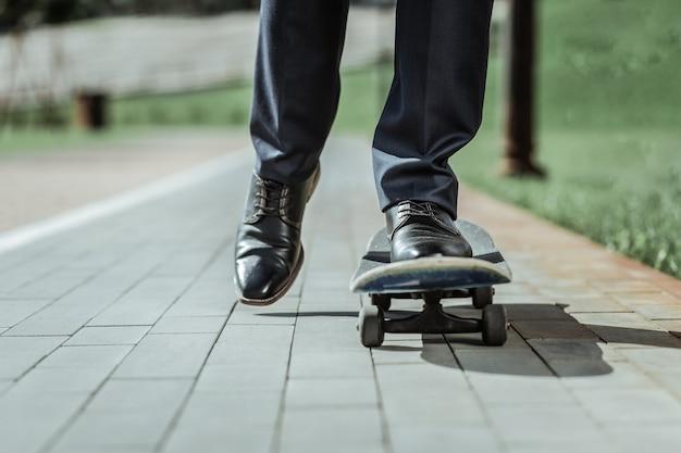 Vlotte rit. close-up van mannelijke voeten staande op oude skateboard tijdens het rijden naar het werk