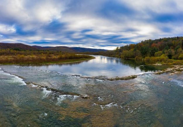 Vlucht over herfst bergrivier, kleurrijke bladeren en stroom striy in carpatian bergen