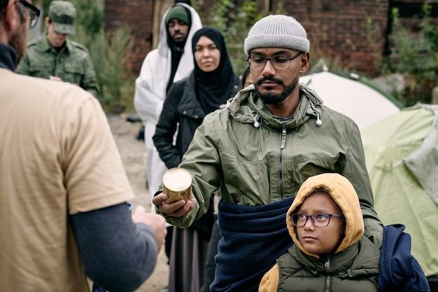 Vluchtelingen die voedselvoorraden ontvangen