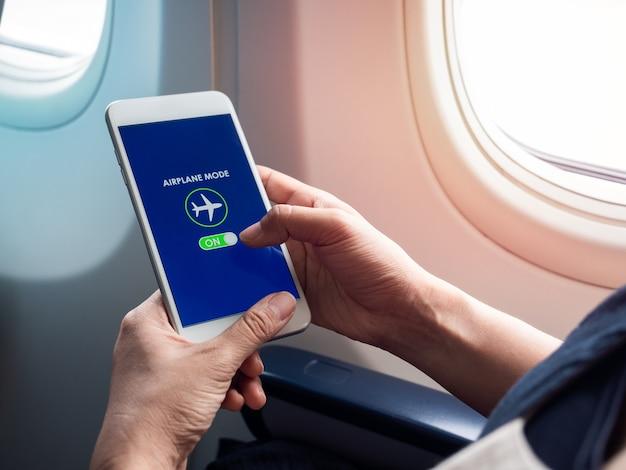 Vluchtmodus concept. hand die witte smartphone houdt en vliegtuigmodus op het scherm dichtbij het venster op het vliegtuig inschakelt.